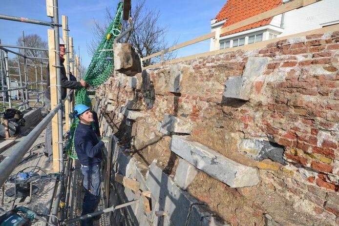 Roy van den Ham en Davey van der Meijden hebben weer een nieuw stuk gevelsteen losgebikt van het Blauwe Bolwerk in Zierikzee. De steen wordt in een netje voorzichtig omlaag gehesen.