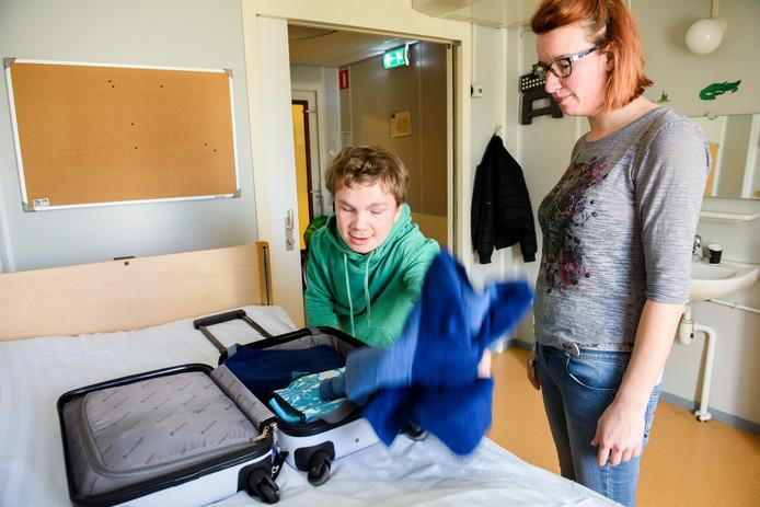 Daan van der Heijden pakt zijn logeerkoffer uit. Rechts kijkt begeleidster Kim Schellekens toe.