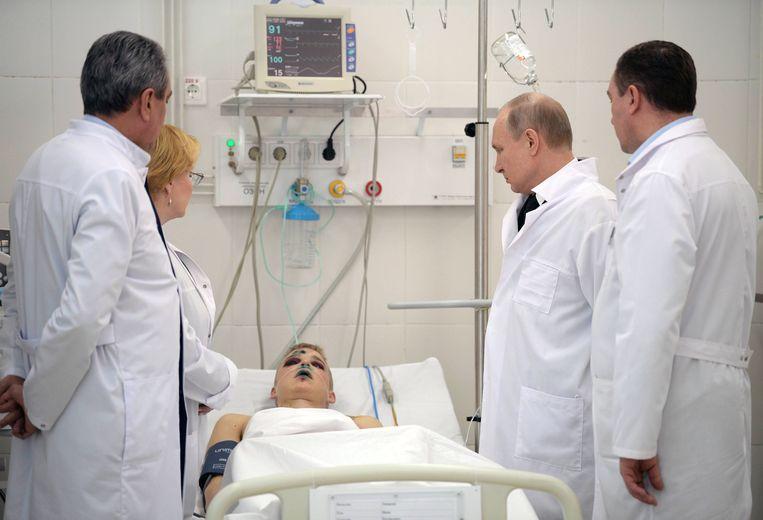 Poetin op bezoek bij een van de slachtoffers. Beeld AFP