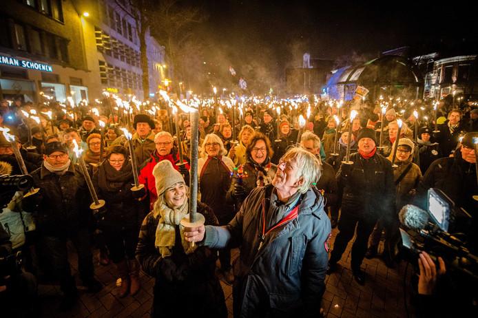 Cabaretier Freek de Jonge loopt mee in een fakkeloptocht door het centrum van de stad in protest tegen de gaswinning in de provincie door de NAM.