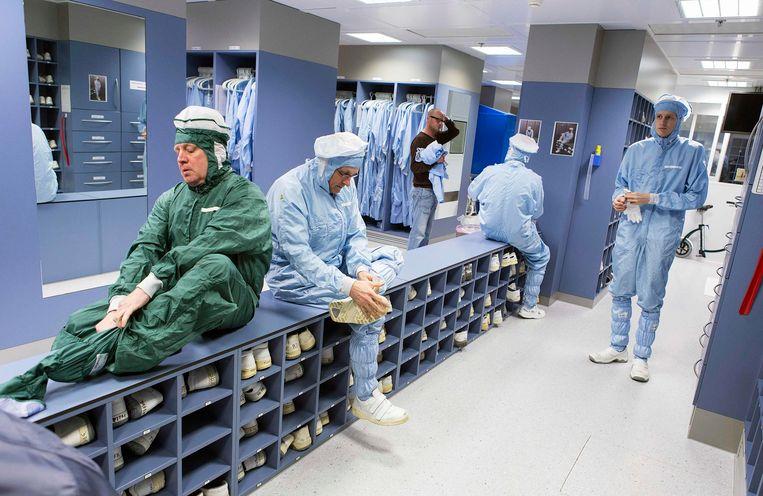 ASML-medewerkers in Veldhoven oen speciale kleding aan om te voorkomen dat stof in de zeer gevoelige apparatuur van het bedrijf komt. Beeld reuters