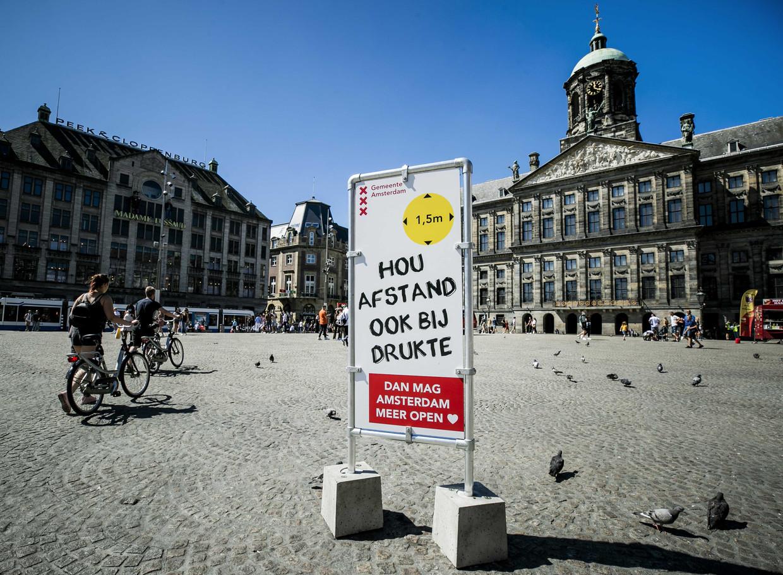 Een informatiebord op de Dam. Het dragen van een mondkapje is verplicht op vijf drukke plekken in de stad, waaronder de Dam en de Kalverstraat.