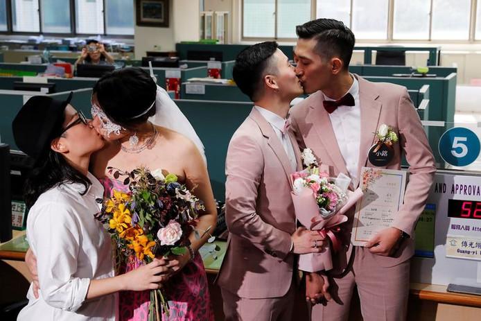 Tortelduifjes Shane Lin en Marc Yuan, en Cynical Chick en Li Ying-Chien, kussen elkaar nadat ze hun huwelijken hebben laten registreren.