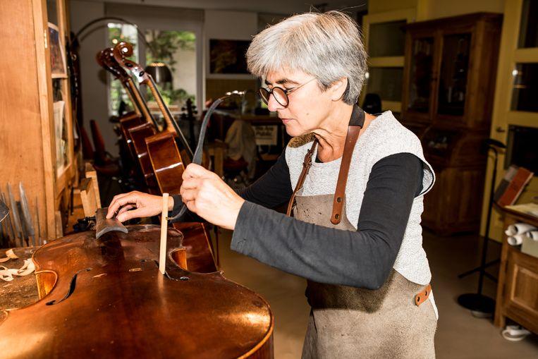 Saskia Schouten plaatst een stapel tussen het boven- en achterblad van een cello. Beeld Jan Mulders