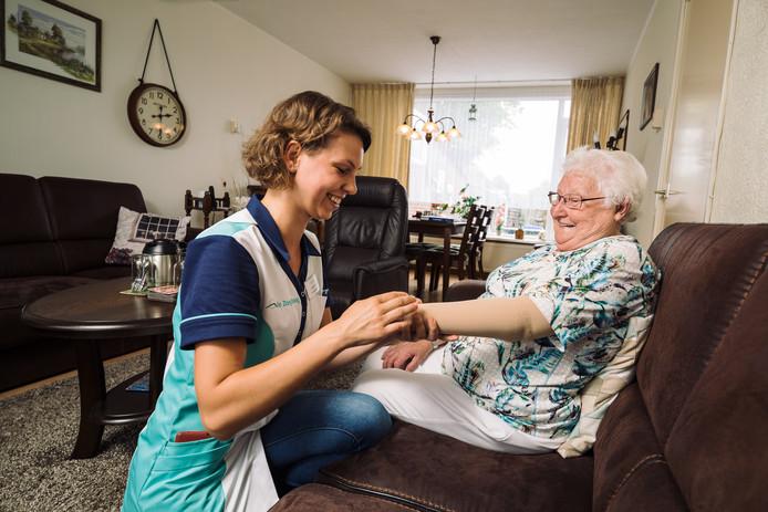 Foto ter illustratie: een wijkverpleegkundige helpt een cliënte.