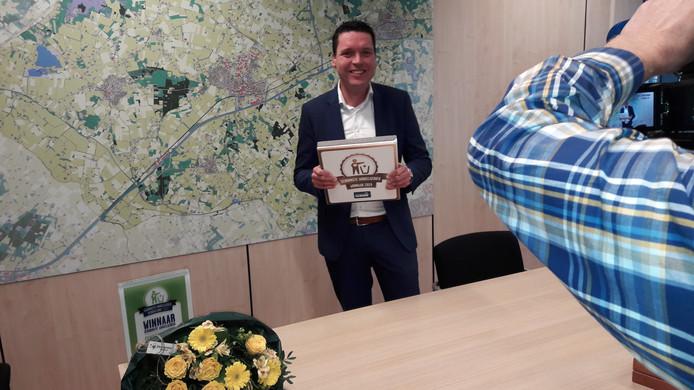 Wethouder Wim Meulenkamp met de vanmorgwn ontvangen 'gouden' stoeptegel waarop staat dat Delden het schoonste winkelgebied van Delden heeft.