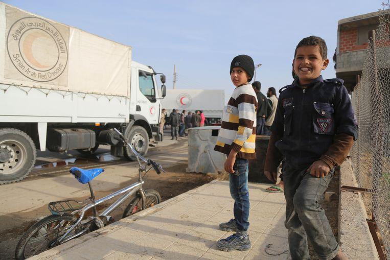 Syrische kinderen bij voertuigen van de Internationale Halve Maan tijdens een levering van humanitaire hulpt in al-Nashabia.