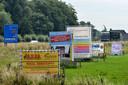 Het schrikbeeld van de provincie Utrecht: reclameborden op een rij in een weiland bij het Gelderse Beusichem.