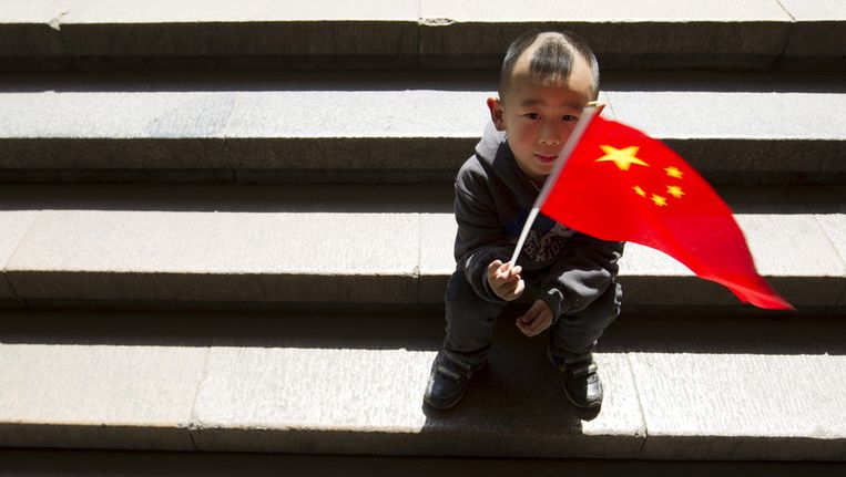 Een Chinees jongetje zwaait met de nationale vlag van China Beeld ap