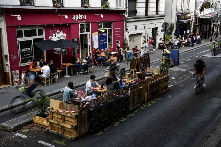 Een voor de coronamaatregelen uitgebreid terras in Parijs.  Beeld AFP