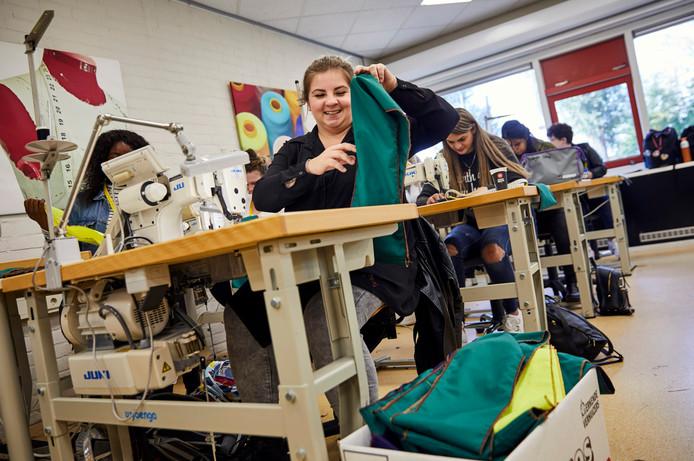 De studenten aan het werk achter de naaimachines op het Albeda College.