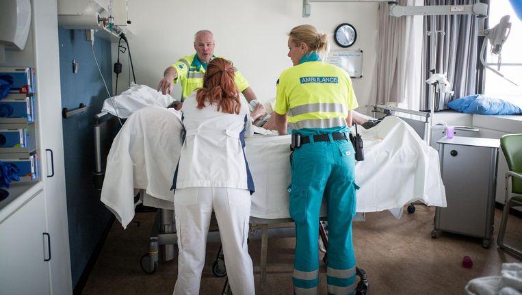 Psychiatrisch verpleegkundige Jessica Hoedeman (r) en een collega bij verward persoon in een ziekenhuis Beeld Peter Valckx