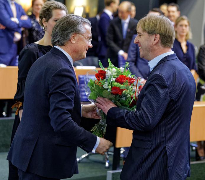 FvD-fractieleider Eric de Bie (rechts) krijgt een bos bloemen van vertrekkend commissaris van de Koning Wim van de Donk. De kans is groot dat Van de Donk (CDA) in september afscheid neemt van een college van GS met daarin één of meer bestuurders van Forum voor Democratie.