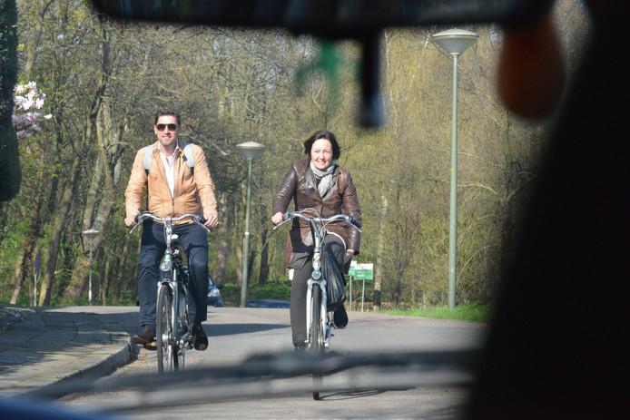 D66'ers Robert van Asten en Saskia Bruines verlaten de stadskwekerij per fiets.