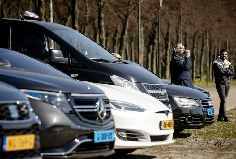 Taxiondernemers verzamelen zich op het Malieveld in Den Haag om een petitie te overhandigen op het ministerie van economische zaken. Beeld ANP