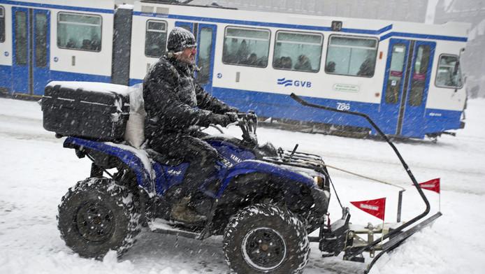 Een sneeuwschuiver op het Rokin met daarachter een tram van het GVB.