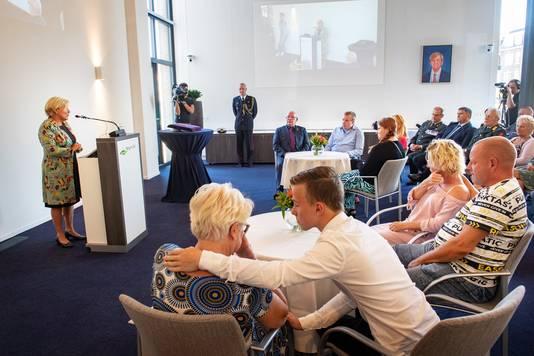 Henk Struijs (achterste tafel, bril), Carla Boland (voorste tafel, rechts) en families luisteren naar de woorden van minister van Defensie Ank Bijleveld in het gemeentehuis in Groesbeek.