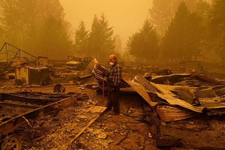 George Coble bij de overblijfselen van zijn door bosbranden verwoeste huis in Oregon.  Beeld AP