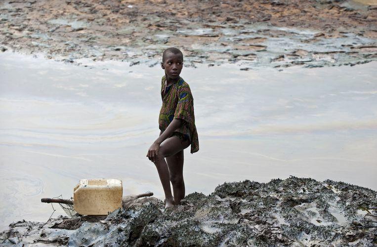 Een jongen met een visnet staat op de met ruwe olie besmeurde oever van een slenk in het krekengebied bij Goi (Ogoniland, Nigeria), dat zwaar verontreinigd is als gevolg van meerdere lekkages uit pijpleidingen van Shell. Beeld anp