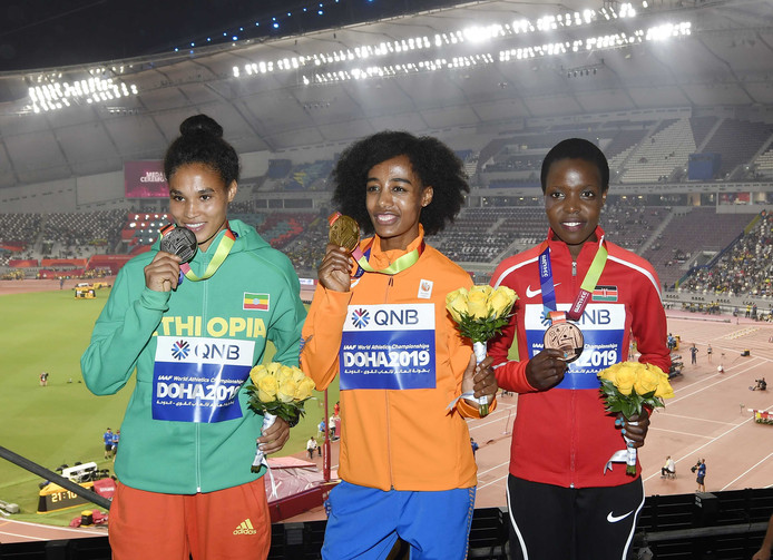 Letesenbet Gidey (Ethiopie, zilver) Sifan Hassan (Nederland, goud) en Agnes Jebet Tirop (Kenia, brons) op het podium na het winnen van de 10.000 meter tijdens de wereldkampioenschappen atletiek in Qatar.
