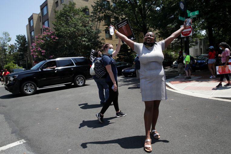 Een activist juicht nadat demonstranten in Washington met een vrachtwagen met een muziekmakende band erop de weg hebben geblokkeerd naar de woning van Mitch McConnell, de leider van de Republikeinse meerderheid in de Senaat. De betogers eisen dat de corona-uitkeringen na 31 juli worden verlengd.  Beeld Jonathan Ernst / Reuters