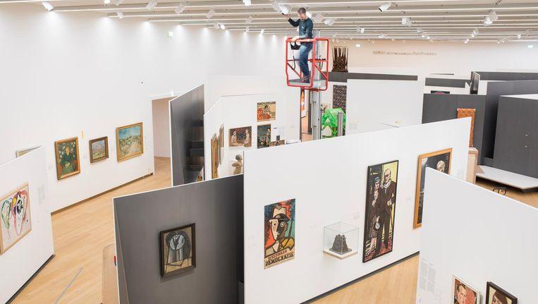 Op speciaal ontworpen slanke, stalen wanden die los in de ruimte staan, zijn werken thematisch bij elkaar gebracht. Beeld Marc Driessen