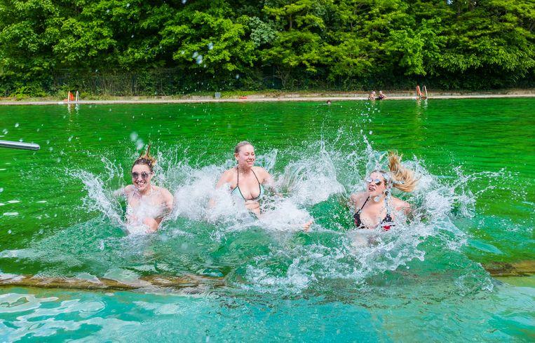 Charlotte, Naiomi en Valerie nemen een verfrissende duik in zwemvijver Boekenberg in Antwerpen.