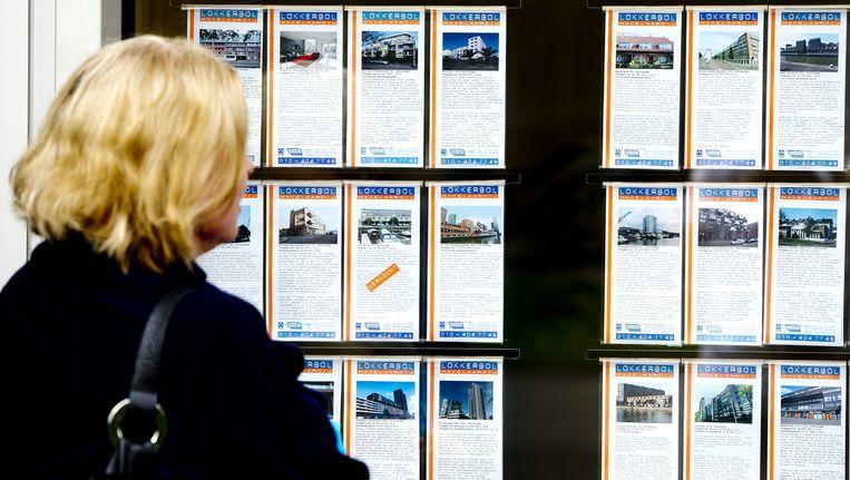 Een vrouw kijkt in de etalage van een makelaar in Rotterdam. Beeld anp