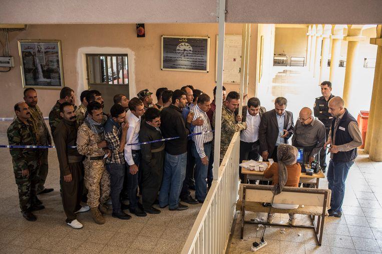 Leden van de Iraakse veiligheidsdienst staan in de rij om hun stembiljetten op te halen tijdens de verkiezingen in Irak. Beeld Getty Images