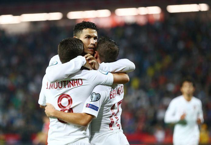 Sporting-exponenten Cristiano Ronaldo en João Moutinho juichen na een treffer van Manchester City-speler Bernardo Silva voor de nationale ploeg van Portugal.