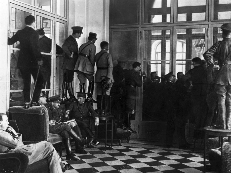 Geallieerde officieren staan op tafels en stoelen om een glimp op te kunnen vangen van de ondertekening van het Verdrag van Versailles.
