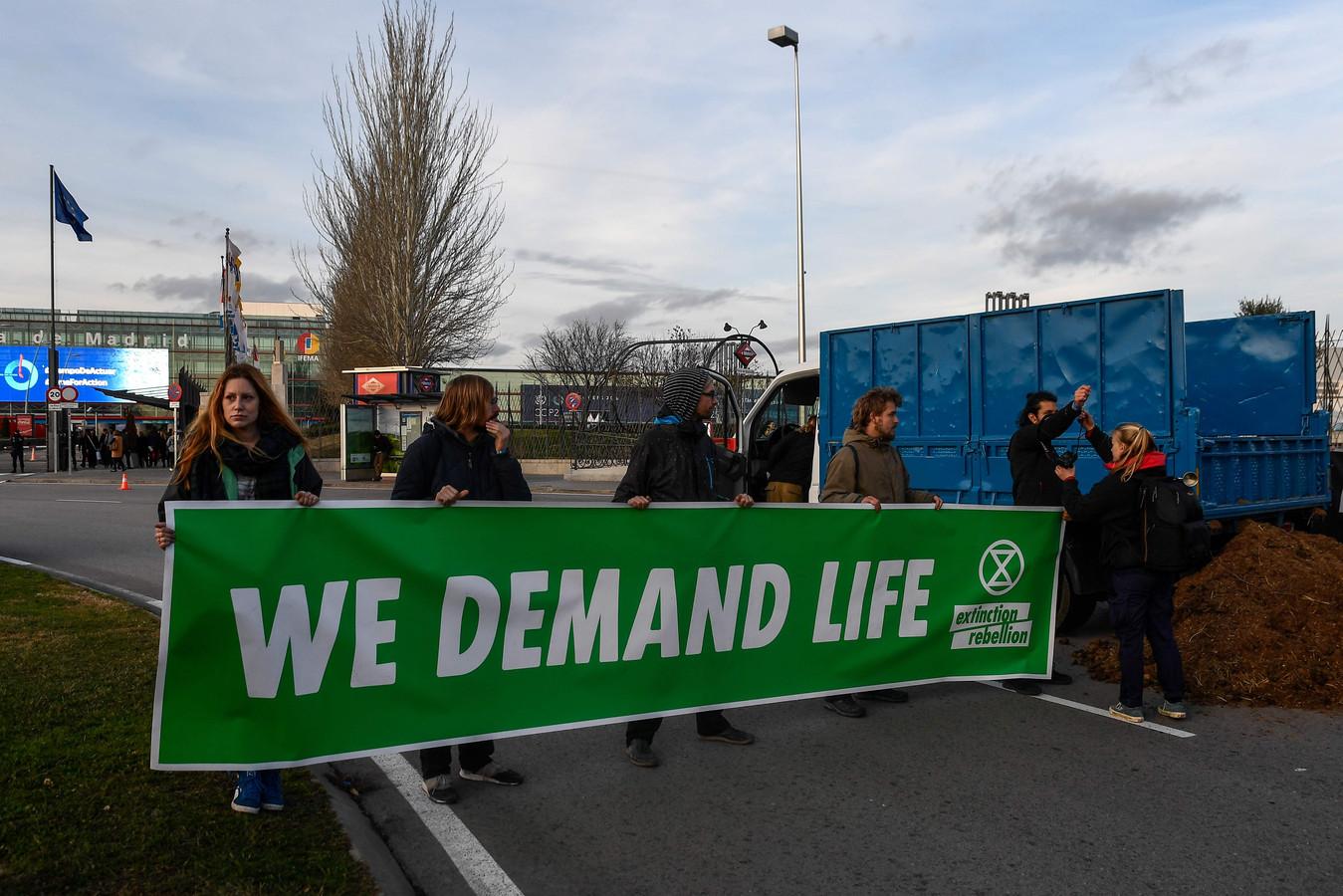 Activisten van de groep Extinction Rebellion stortten uit protest kunstmest voor de deur van het conferentiecentrum in Madrid.