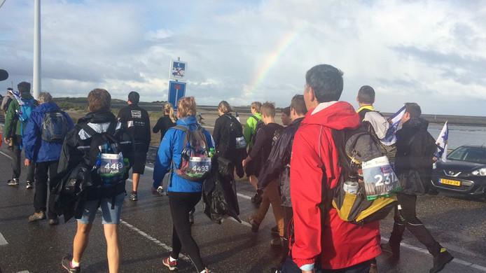 Wandelaars kijken bij Neeltje Jans naar de regenboog.