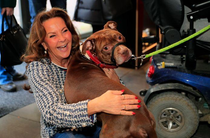 Initiatiefneemster Anita Verweij van de dierenvoedselbank wordt bij de opening omver gesprongen door pitbull Dingo.
