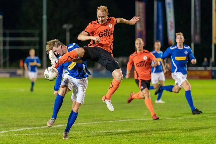 Luuk Pelkman van RKHVV duikt weg voor Max de Wijze van De Bataven in de Betuwse derby der derby's.