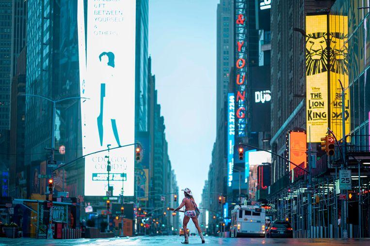 Times Square in New York is verlaten, op een straatmuzikant na die bekendstaat als The Naked Cowboy.  Beeld AFP