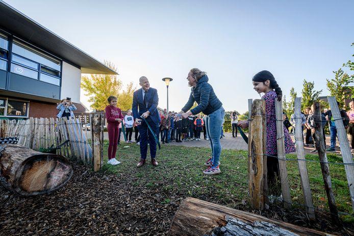 Opening tiny forest bij basisschool Het Letterveld. Leerkracht Rimke Gerritsen en wethouder Alex Langius knippen lintje door, dat wordt vastgehouden door Ilayda (links) en Elisa.