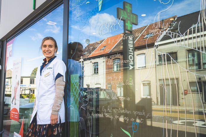 Apothekeres Dorien De Vylder naast haar gedicht op het raam van de zaak in de Gentse Morekstraat.