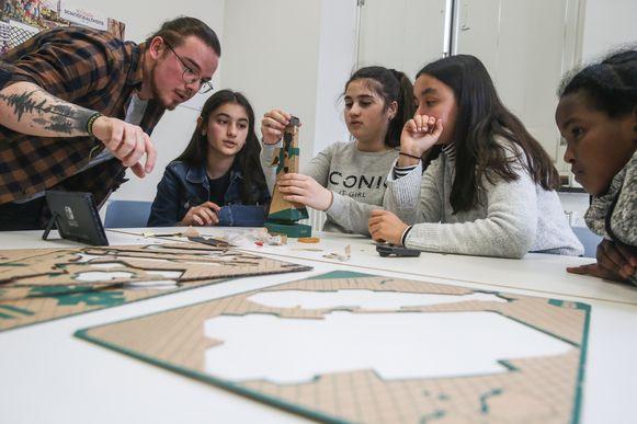Leerkracht Lander Van der Biest steekt de leerlingen een handje toe bij het bouwen van het Nintendo Labo-pakket.