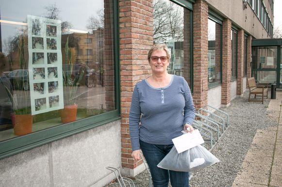 """Claire Maes bij de fotocollage aan rusthuis Populierenhof in Nieuwerken, waar ze net de was is komen ophalen van haar vader. """"Op 5 april wordt hij 85 jaar. Het zal heel vreemd zijn om dat niet samen te kunnen vieren."""""""