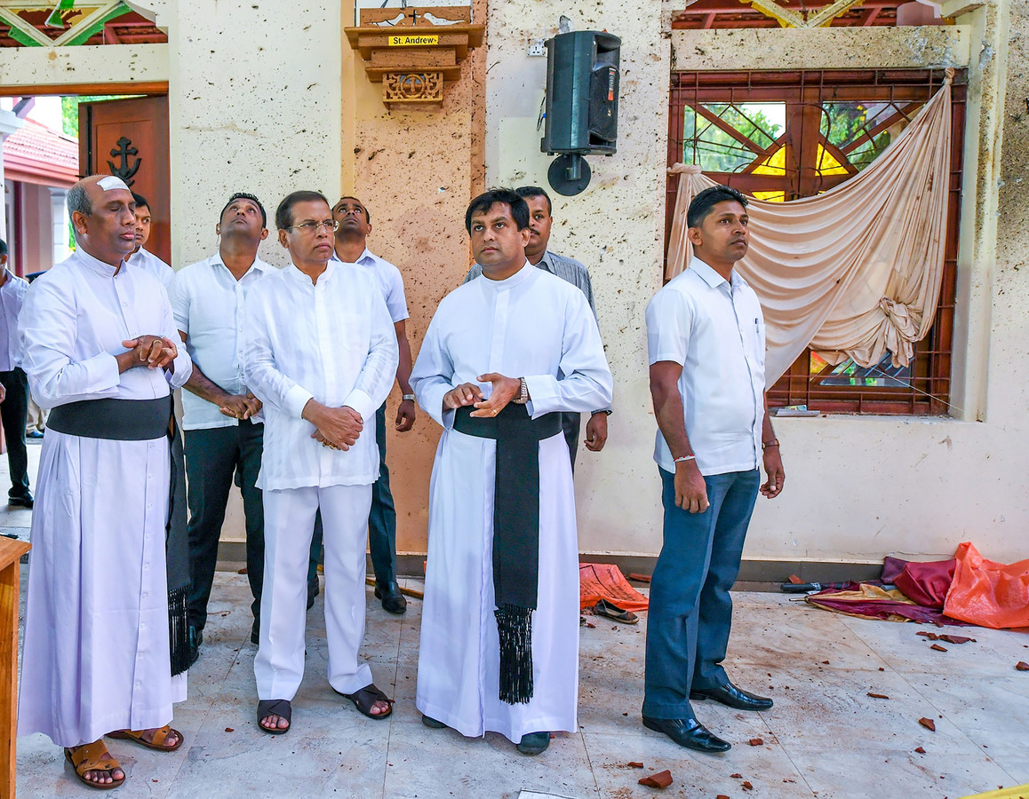 President Maithripala Sirisena (derde van links) bezoekt de  St. Sebastian's kerk in Negombo, twee dagen na de aanslagen.
