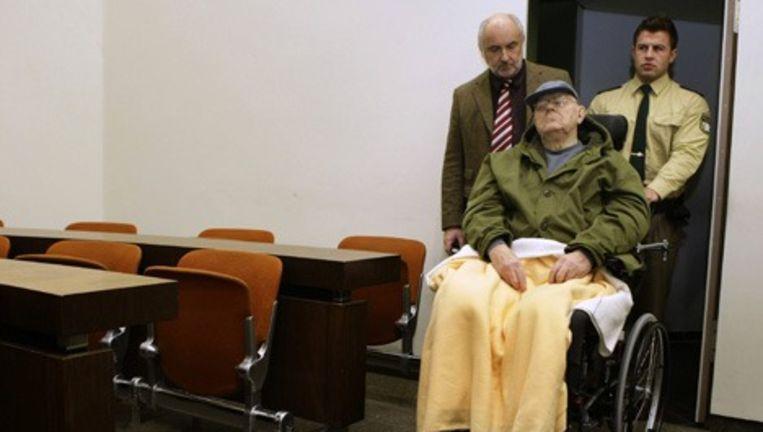 John Demjanjuk (89) had maandag bij de hervatting van zijn proces in München weer zijn blauwe basketballpet op. Hij zag er fitter uit dan bij de eerdere zittingen, enkele weken geleden. Foto AP Beeld