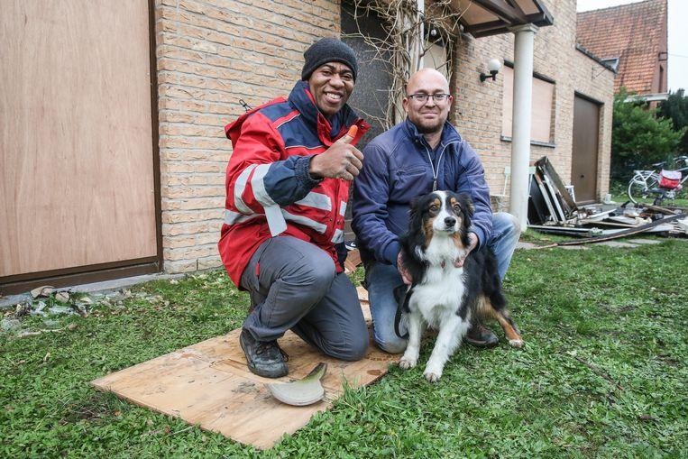 Postbode Nsinga Serge en bewoner Philip Bernard met zijn hond Fanny.
