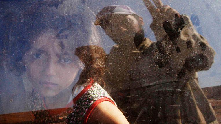 Een meisje ontvlucht de strijd in Bani Walid op het hoogtepunt van de opstand tegen Moammar Kaddafi. (foto van september 2011) Beeld REUTERS