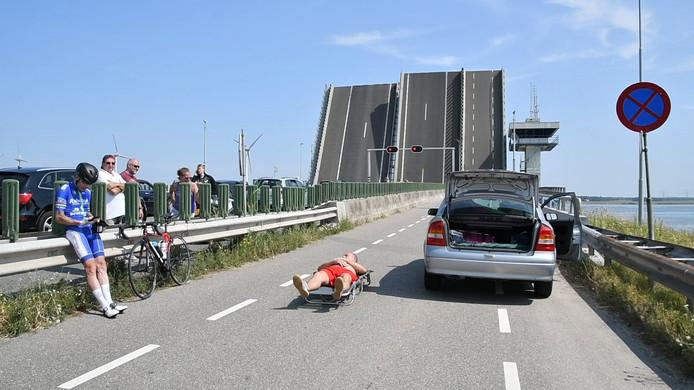 De Ketelbrug tussen Emmeloord en Lelystad had eind juli te maken met een storing. De brug stond open voor de scheepvaart, vervolgens trad de storing op. Wachtende automobilisten probeerden er het beste van te maken in de zon.  BEELD GinoPress