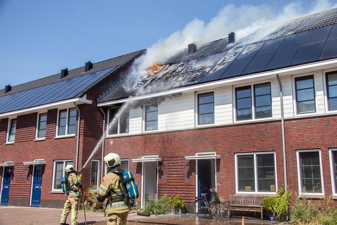 Brandweerlieden bestrijden de vlammen op het dak van drie getroffen woningen in Vinkeveen deze week.