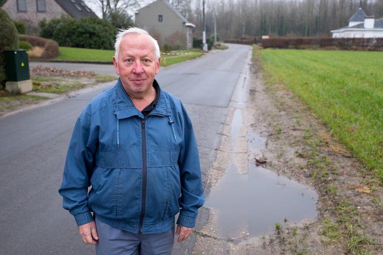 Bewoner Frank Troch toont de verzakkingen en de slechte afwatering in de straat.