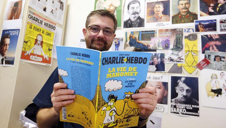 Hoofdredacteur Charb met La Vie de Mahomet in handen. Beeld AFP