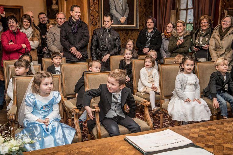 De kindjes komen aan met een oldtimer en nemen plaats in de trouwzaal.