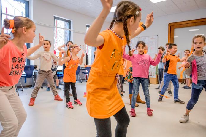 Kinderen van basisschool De Oase en De Hietweide oefenen  in Twello hun dansje op de Fitlala voor de Koningsspelen.